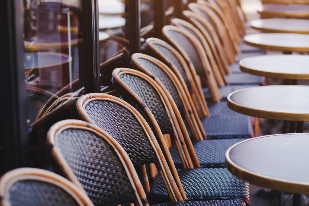 row of whicker chairs and tables in traditional sidewalk cafe in Paris
